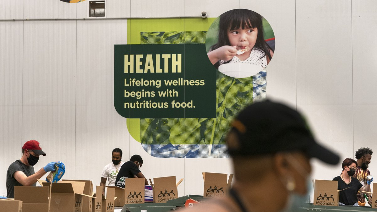 Volunteers pack boxes of food for distribution, at The Capital Area Food Bank, Tuesday, Oct. 5,...