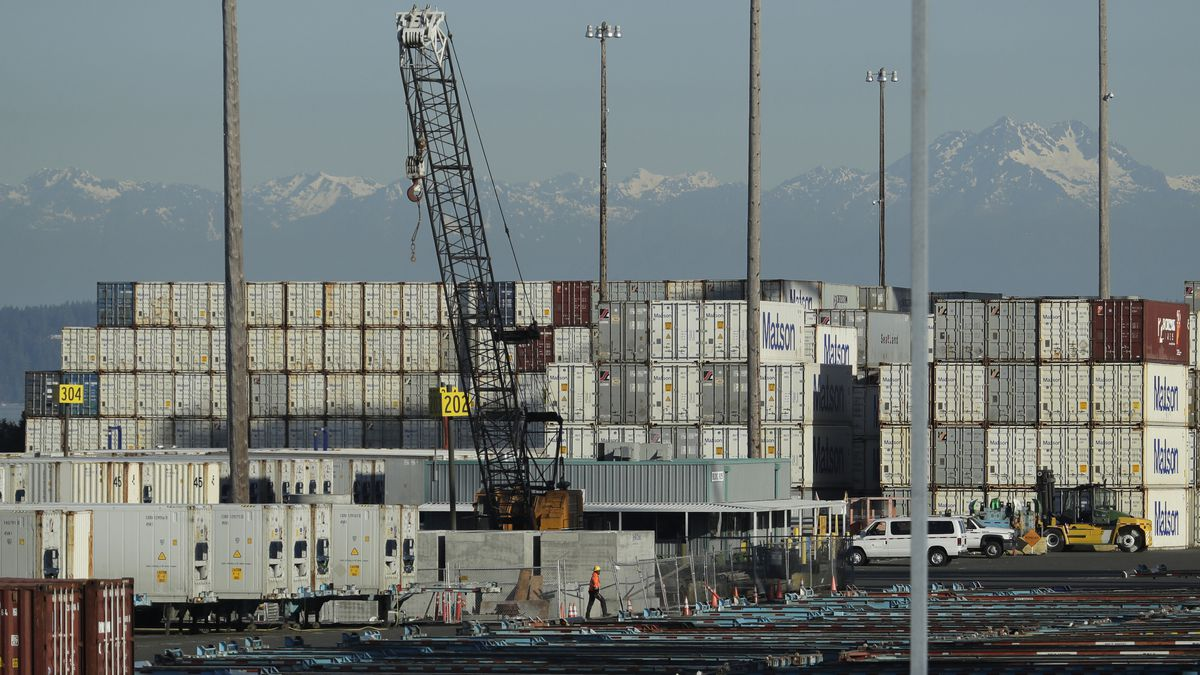 FILE - In this May 10, 2019 file photo, a worker walks near truck trailers and cargo containers at the Port of Tacoma in Tacoma, Wash.