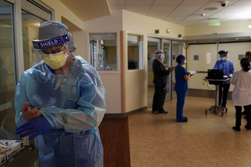 FILE - In this Jan. 7, 2021 file photo, registered nurse Merri Lynn Anderson puts on her...