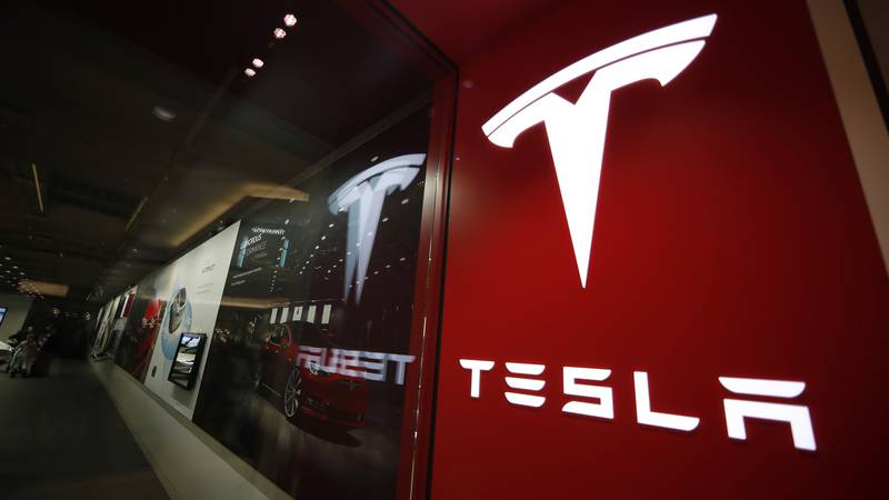 FILE - This Feb. 9, 2019 file photo shows a sign bearing the company logo outside a Tesla store...