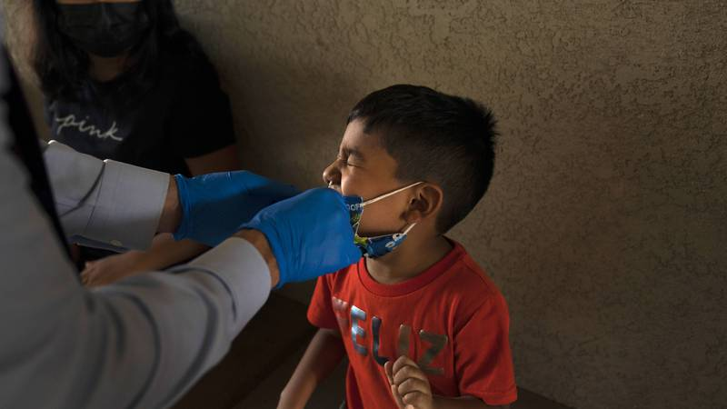 Shahir Sanchez, 5, grimaces as Dr. Neal Schwartz collects a nasal swab sample for COVID-19...