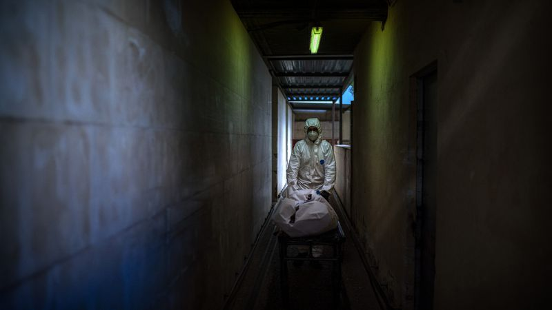 FILE - In this Nov. 5, 2020, file photo, mortuary worker transports the body of a COVID-19...