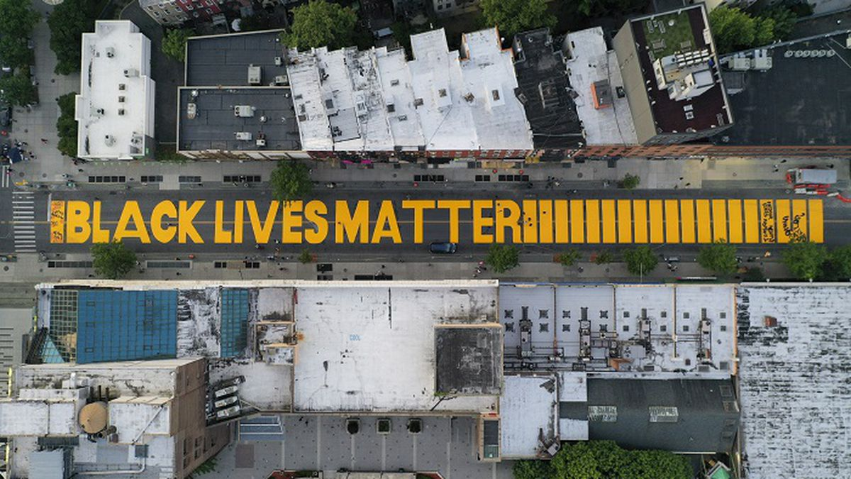 """A giant """"BLACK LIVES MATTER"""" sign is painted in orange on Fulton Street, Monday, June 15, 2020, in the Brooklyn borough of New York. (Source: AP Photo/John Minchillo)"""